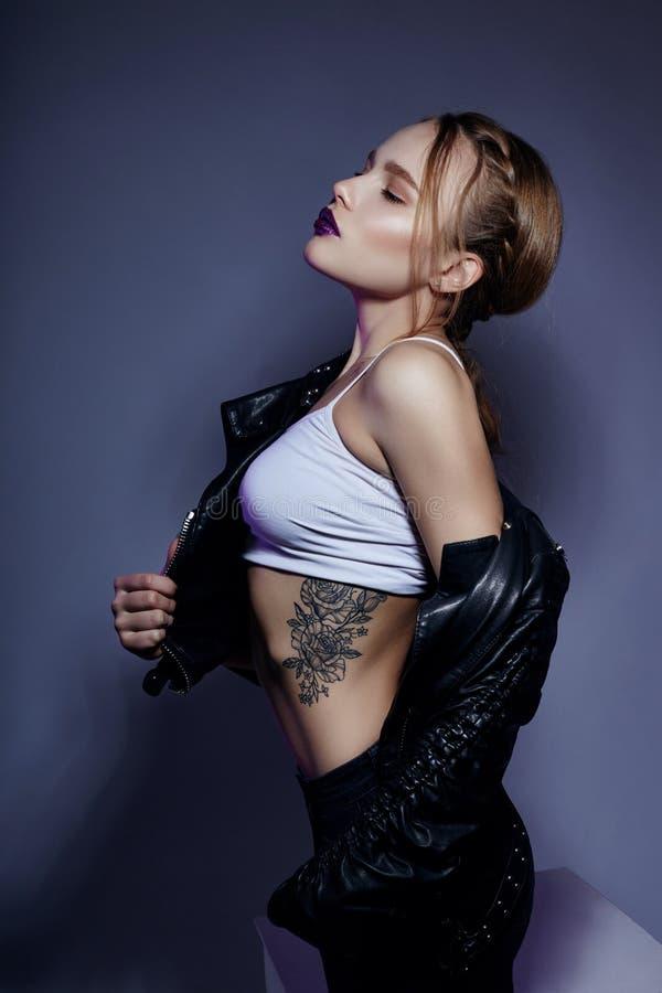 Menina loura 'sexy' com tatuagem no casaco de cabedal e nas calças de brim, portra fotografia de stock royalty free
