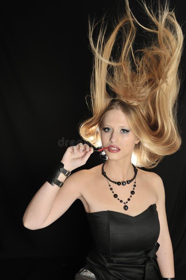 A menina loura 'sexy' come pimentões vermelhos fotografia de stock