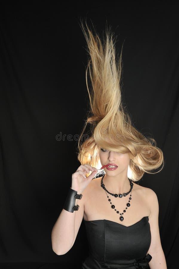 A menina loura 'sexy' come pimentões vermelhos fotografia de stock royalty free
