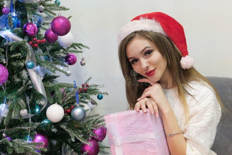 Menina loura 'sexy' em uma camiseta feita malha e em um tampão vermelho como Santa Claus felizmente e olhares bonitos na câmera a imagem de stock