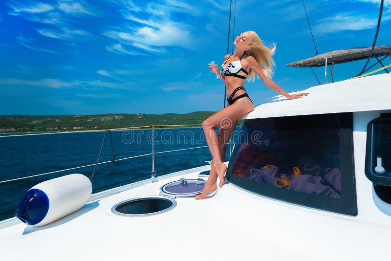 Menina loura 'sexy' nova bonita em um terno de nadada em um iate que guarda o vidro do vinho no dia de verão ensolarado Cro?cia e fotografia de stock