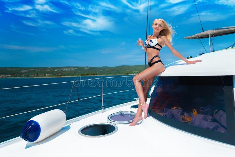 Menina loura 'sexy' nova bonita em um terno de nadada em um iate que guarda o vidro do vinho no dia de verão ensolarado Cro?cia e imagens de stock royalty free