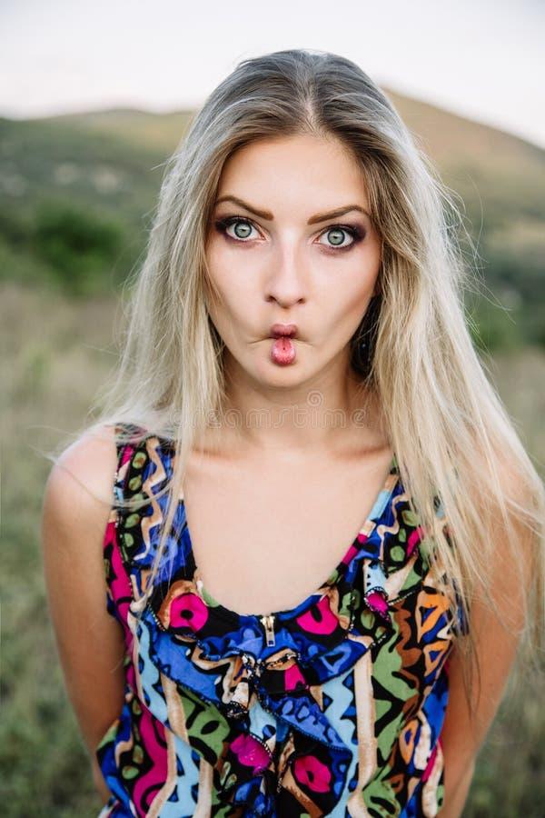 Menina loura sonhadora bonita com olhos azuis em um vestido leve de turquesa que encontra-se nas pedras fotografia de stock