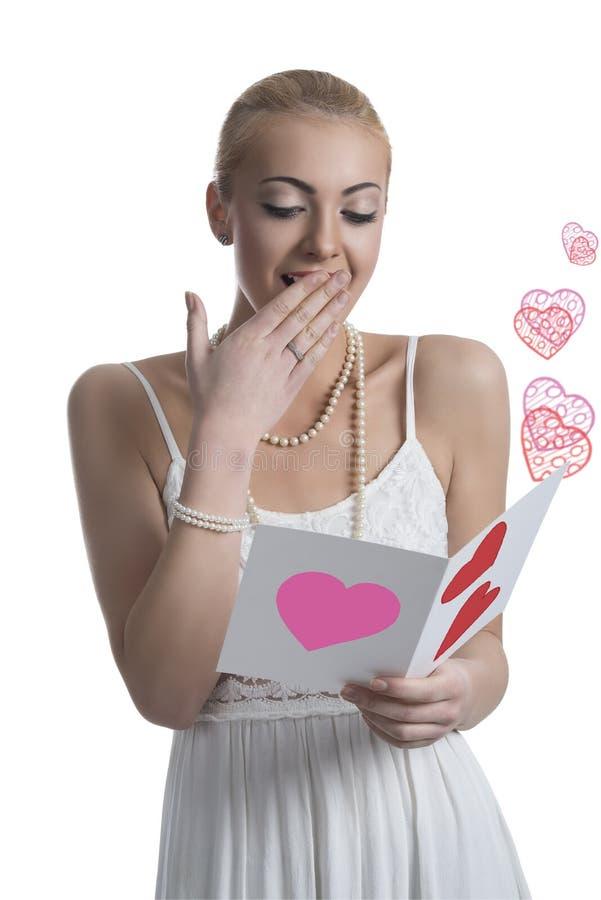 A menina loura surpreendida lê o cartão do Valentim foto de stock