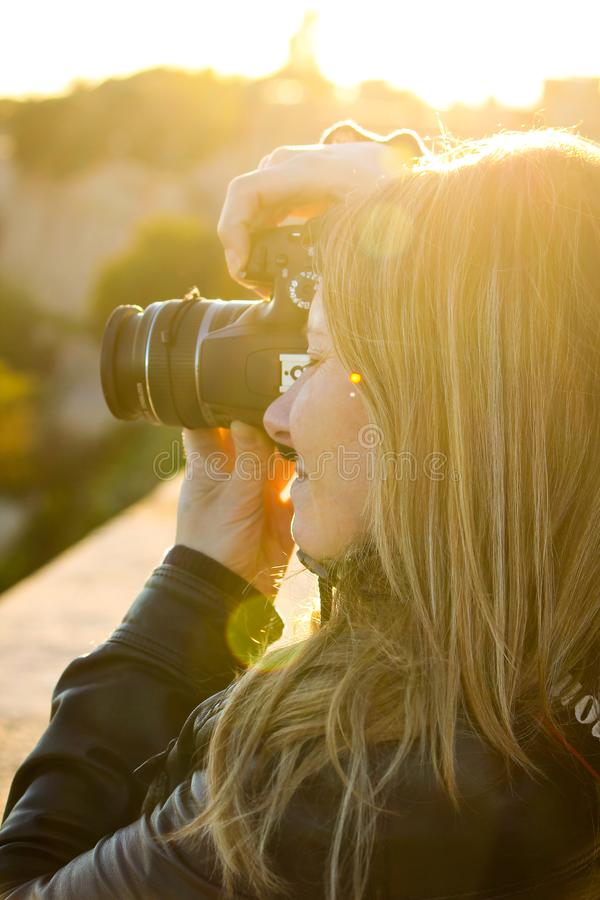 A menina loura toma fotos com reflexo fotos de stock royalty free