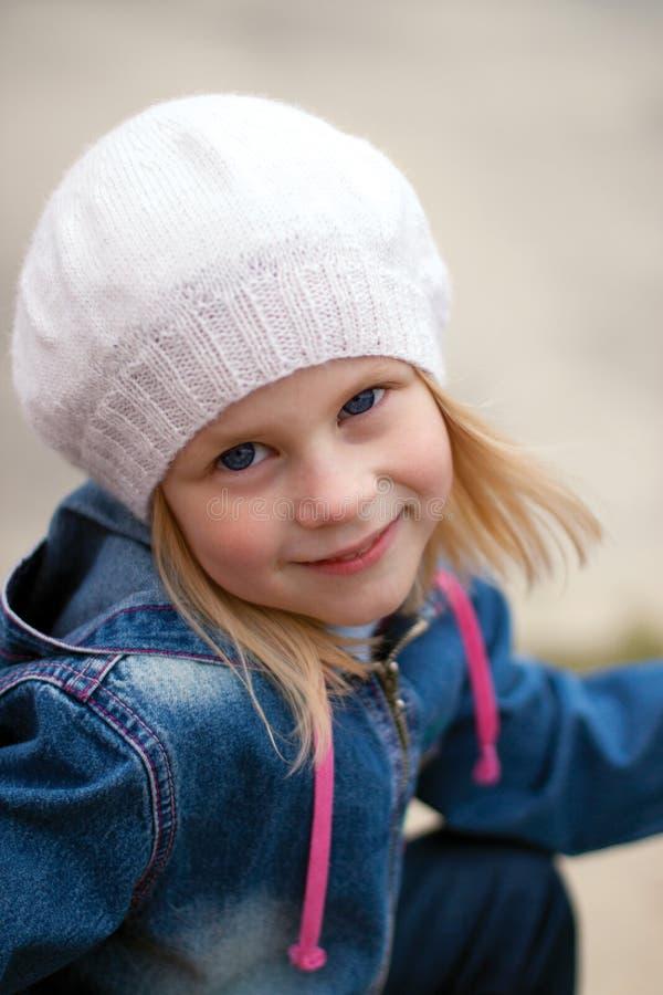 A menina louro-de cabelo feliz em um chapéu branco com os olhos largos abre fotografia de stock