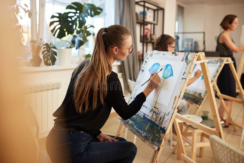 A menina louro de encantamento nos vidros vestidos na blusa e em calças de brim pretas senta-se na armação e pinta-se uma imagem  imagens de stock