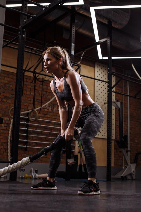 A menina louro nova está indo balançar cordas da batalha fotografia de stock