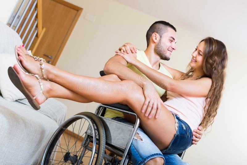 Menina loving com seu noivo na cadeira de rodas imagem de stock