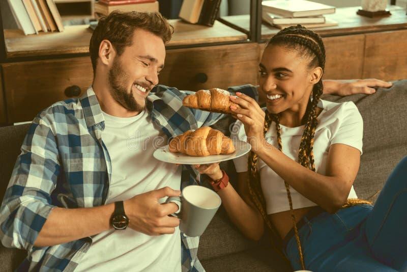 Menina loving que trata o noivo ao croissant imagens de stock royalty free