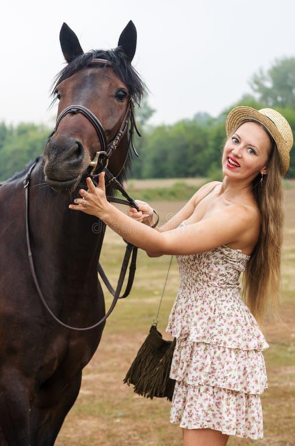 a menina Luz-de cabelo em um chapéu de palha e o verão vestem-se, são fotografados com um cavalo imagens de stock royalty free