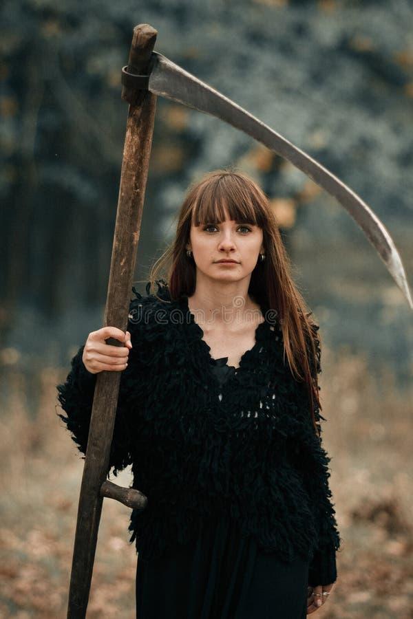 Menina místico misteriosa bonita com cabelo longo no vestido preto que guarda uma trança na floresta escura do outono na maneira  imagens de stock royalty free