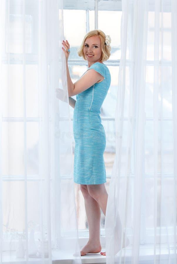 Menina macia bonita que está atrás das cortinas brancas imagens de stock royalty free