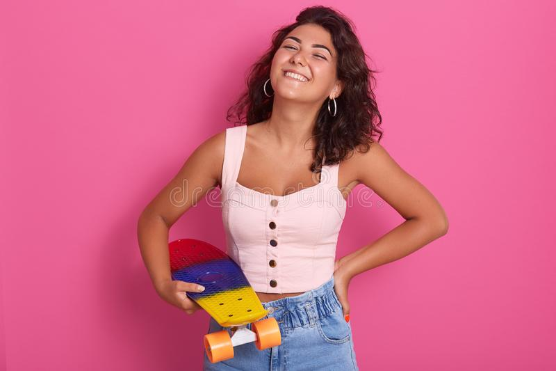 Menina magnífica com sorriso de encantamento na roupa elegante ocasional que levanta com o skate nas mãos Retrato do est?dio de b fotos de stock