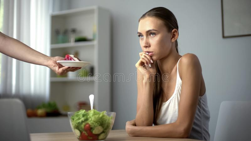 Menina magra que escolhe entre a salada e o bolo, dieta saudável contra o alimento de alto-caloria foto de stock royalty free