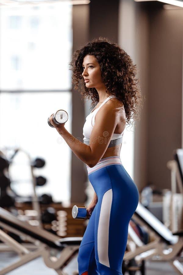 A menina magro com o cabelo encaracolado escuro vestido em um sportswear est? fazendo exerc?cios com pesos no gym moderno com gra imagens de stock