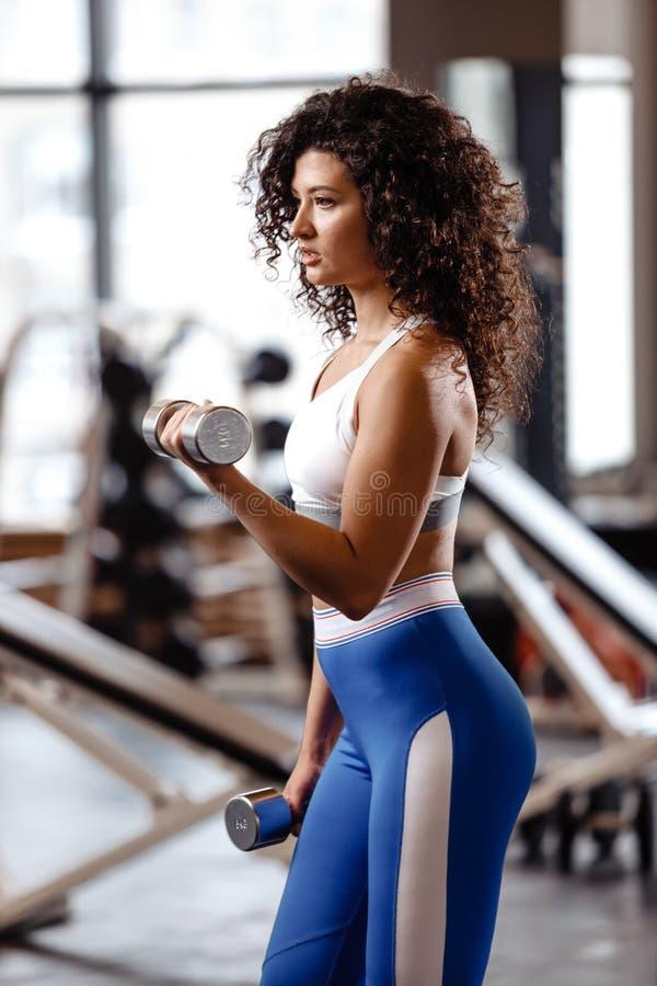 A menina magro com o cabelo encaracolado escuro vestido em um sportswear est? fazendo exerc?cios com pesos no gym moderno com gra fotografia de stock royalty free