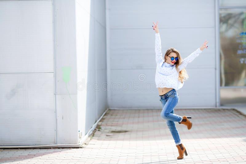 Menina magro fascinante com o cabelo branco que salta e que canta, apreciando o bom dia de verão Jovem mulher engraçada com pele  fotografia de stock