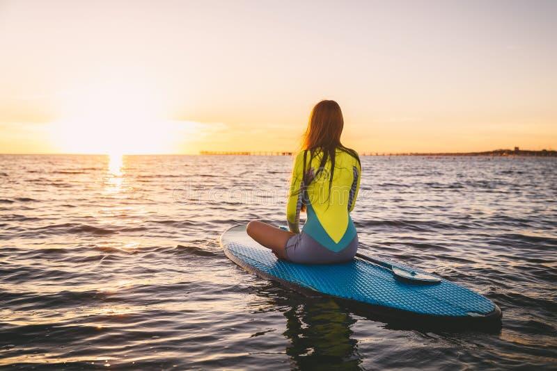 A menina magro levanta-se sobre a placa de pá em um mar quieto com cores do por do sol do verão Relaxamento no oceano imagem de stock royalty free
