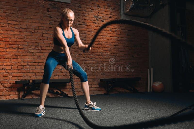 Menina magro loura impressionante 'sexy' que faz exercícios com cordas fotos de stock royalty free