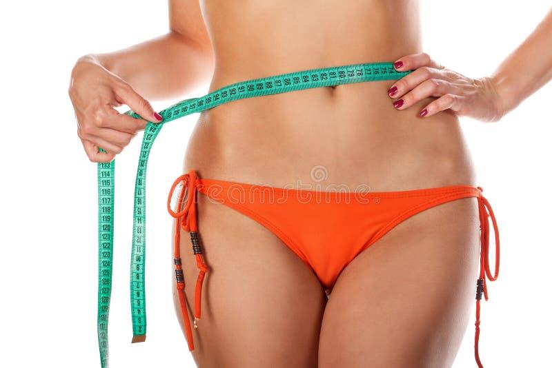 Menina magro na cintura de medição do roupa de banho foto de stock royalty free
