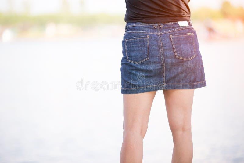 Menina magro na saia curto da sarja de Nimes, vista traseira, close-up foto de stock