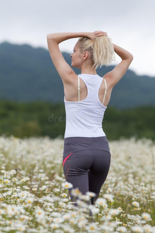 Menina magro no sportswear no campo da camomila imagem de stock