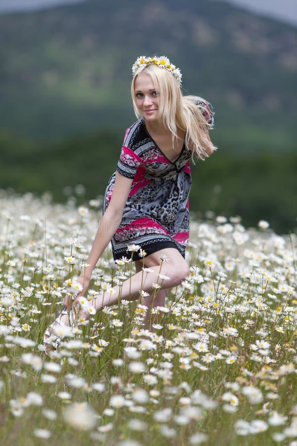 Menina magro no vestido leve que anda no campo da camomila imagens de stock