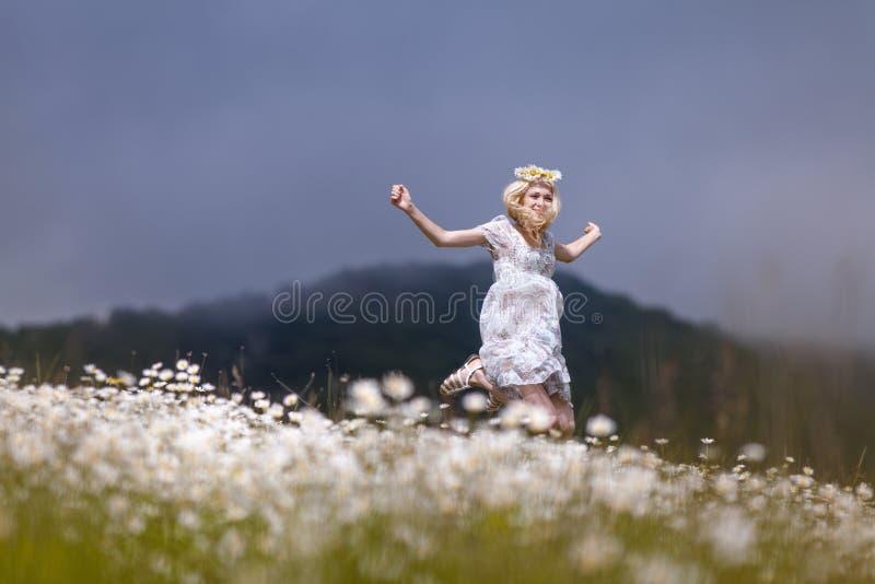 Menina magro no vestido leve que salta no campo da camomila foto de stock royalty free