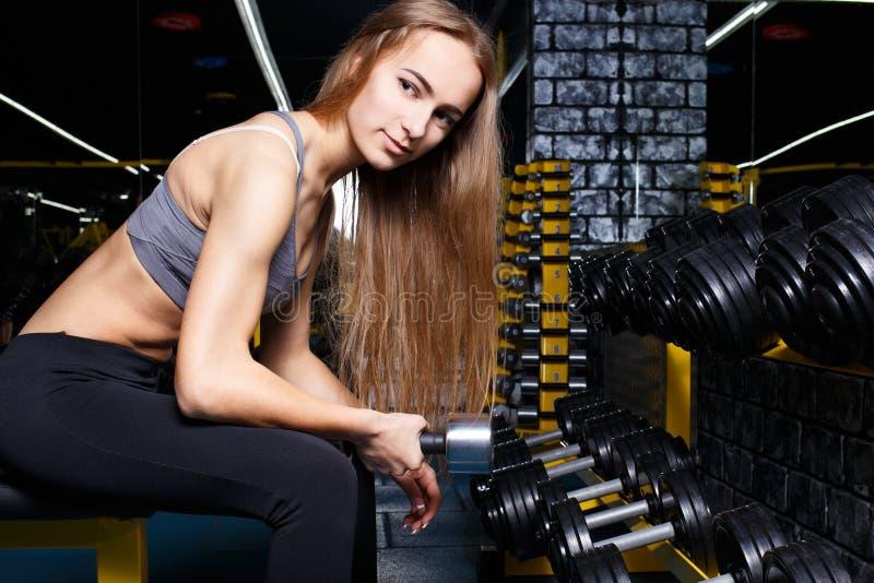 A menina magro nova que faz o bíceps ondula com dumbbels fotos de stock royalty free