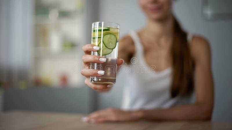 A menina magro oferece a bebida com os vegetais para a pele saudável, equilíbrio de água do corpo fotos de stock royalty free