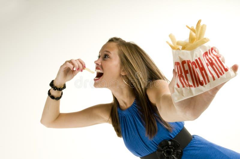 Menina magro que come fritadas do francês fotos de stock