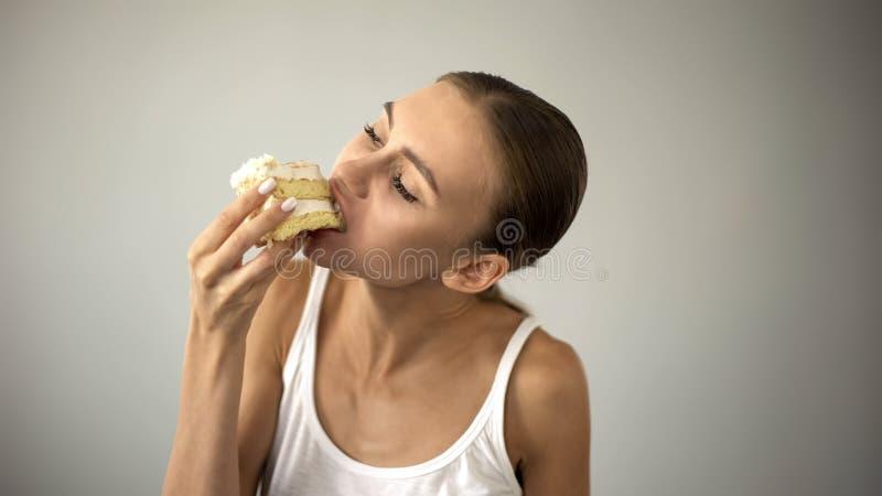 Menina magro que come o bolo ansiosamente, fazendo dieta e morrendo de fome, falta do autodisciplina imagem de stock royalty free