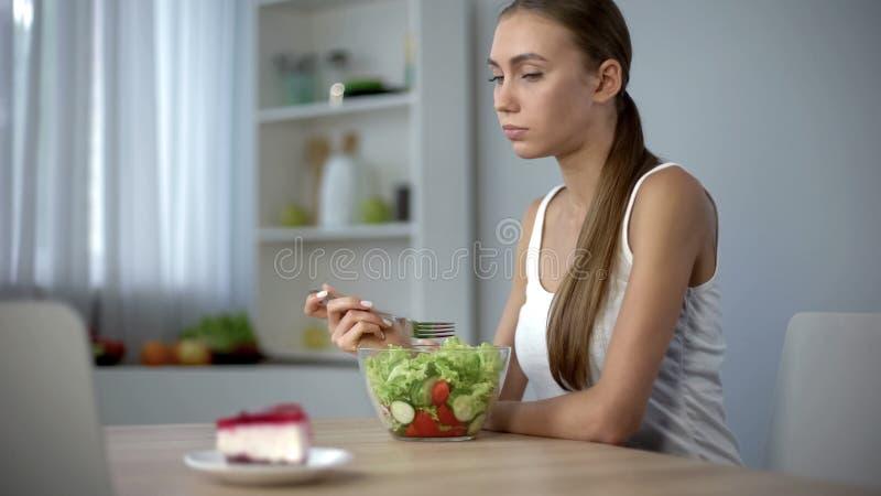 Menina magro que come a salada mas o bolo da ânsia, tendência da forma ser delgado, dieta imagem de stock royalty free