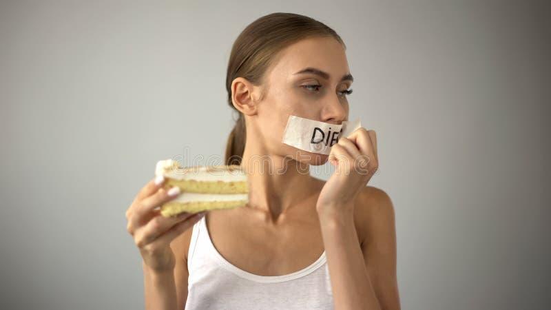 A menina magro que escolhe comer o bolo, decolando a fita da boca, para de fazer dieta, tentação imagens de stock
