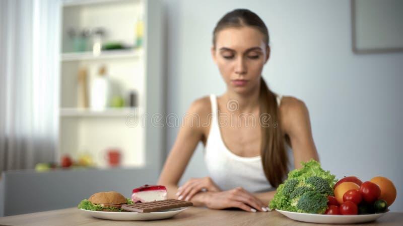 Menina magro que escolhe entre a comida lixo e vegetais saudáveis, hesitação, dieta imagem de stock