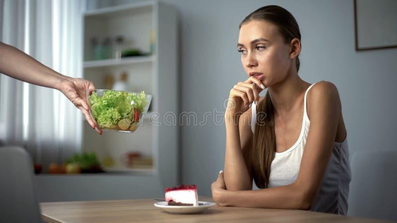 Menina magro que pensa sobre a decisão para comer o bolo ou a salada, calorias contra a dieta saudável fotografia de stock