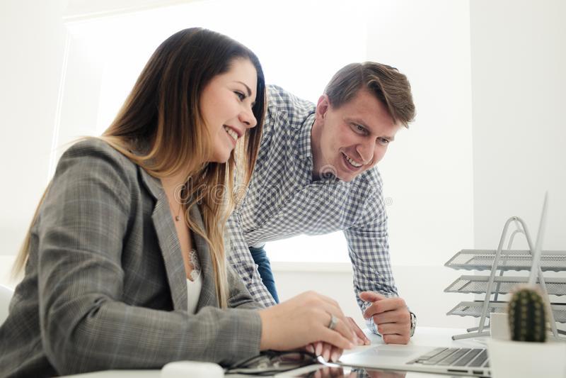 Menina mais nova e homem que trabalham no escritório na tabela imagem de stock royalty free