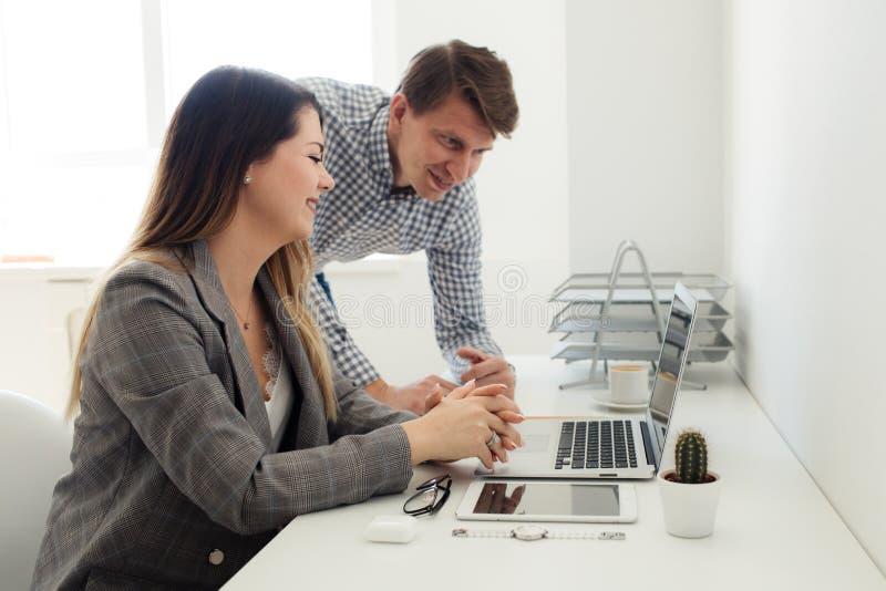 Menina mais nova e homem que trabalham no escritório na tabela imagem de stock