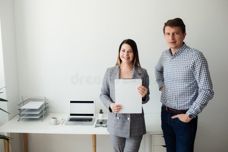 Menina mais nova e homem que trabalham no escritório na tabela fotografia de stock royalty free