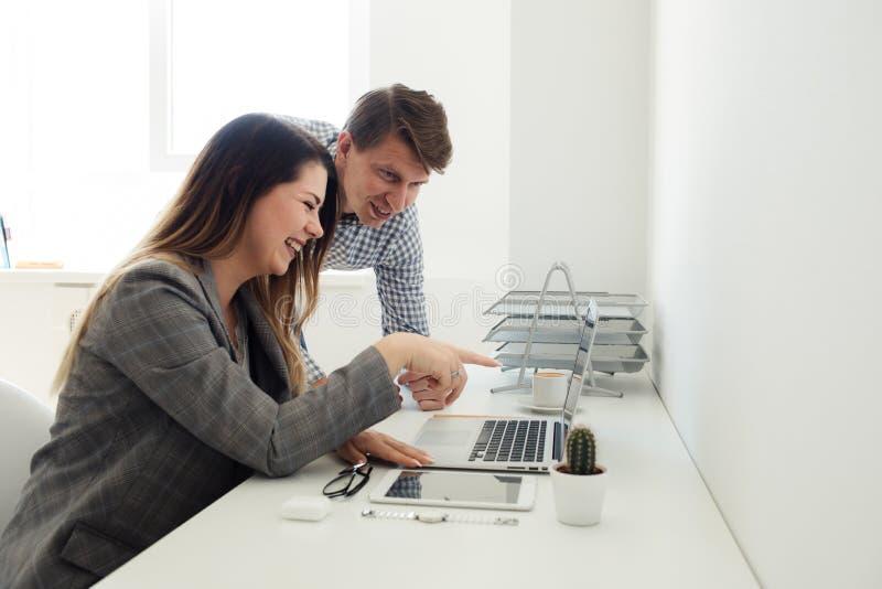 Menina mais nova e homem que trabalham no escritório na tabela foto de stock
