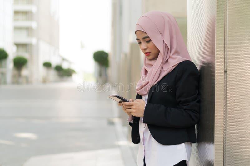 Menina malaio bonita que mantém o telefone celular exterior imagens de stock royalty free