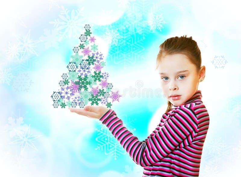 A menina mantém a árvore de abeto feita de multi flocos de neve coloridos imagem de stock