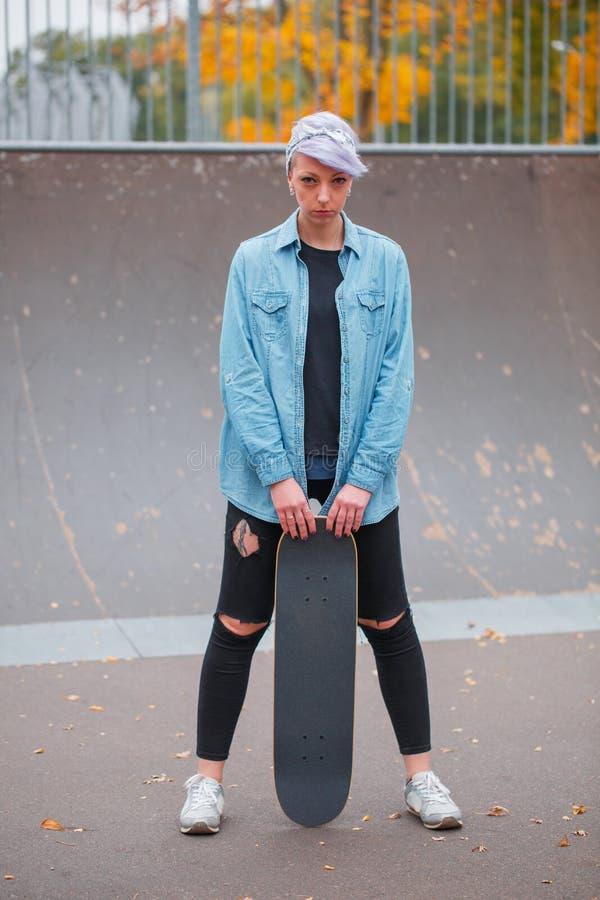A menina mantém sua ombro-largura dos pés separada e guarda um skate no parque do patim imagem de stock royalty free