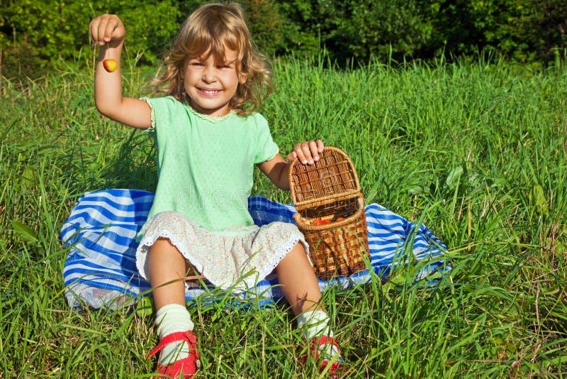 A menina mantem cerejas doces disponivéis fotografia de stock
