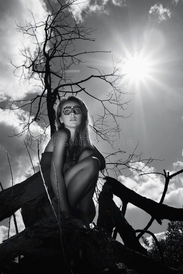 Menina mascarada que senta-se na madeira imagem de stock royalty free