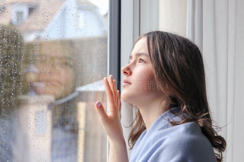 Menina melancólica bonita do adolescente na luz - xaile azul que olha exterior através dos pingos de chuva na janela molhada foto de stock royalty free
