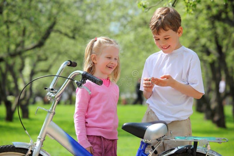 Menina, menino e bicicleta no parque imagem de stock