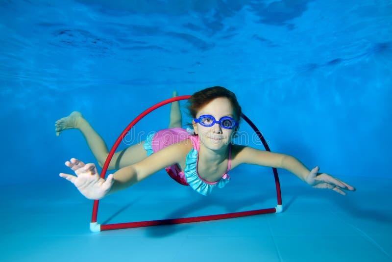 A menina mergulha e nada através da aro na parte inferior da associação que olha a câmera e o sorriso Retrato fotografia de stock