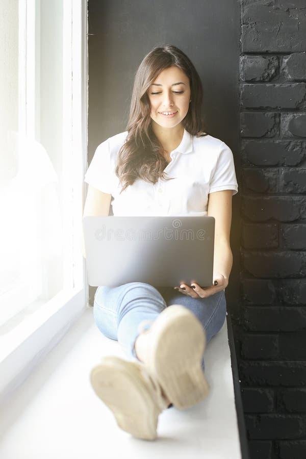 Menina milenar feliz com o portátil na soleira Retrato da jovem mulher com diferença do diastema entre os dentes Sorriso bonito i imagens de stock